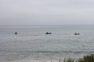 Boats using nets to encircle the oil and try to sweep it up.